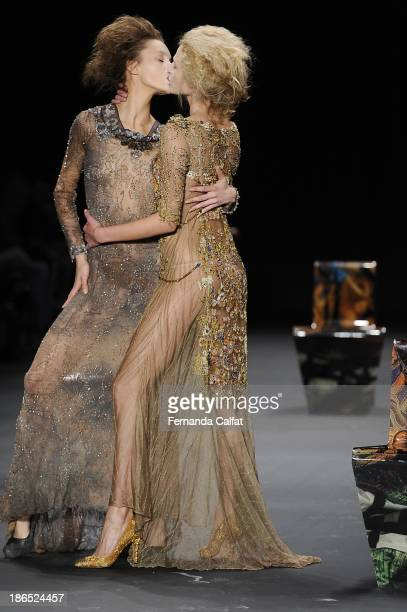 Izabel Hickman and Alicia Kuczman kiss each other on the runway during Lino Villaventura show at Sao Paulo Fashion Week Winter 2014 on October 31...