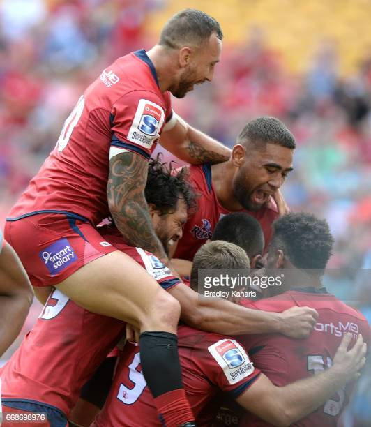 Izaia Perese of the Reds is congratulated by team mates after scoring a try during the round eight Super Rugby match between the Reds and the Kings...