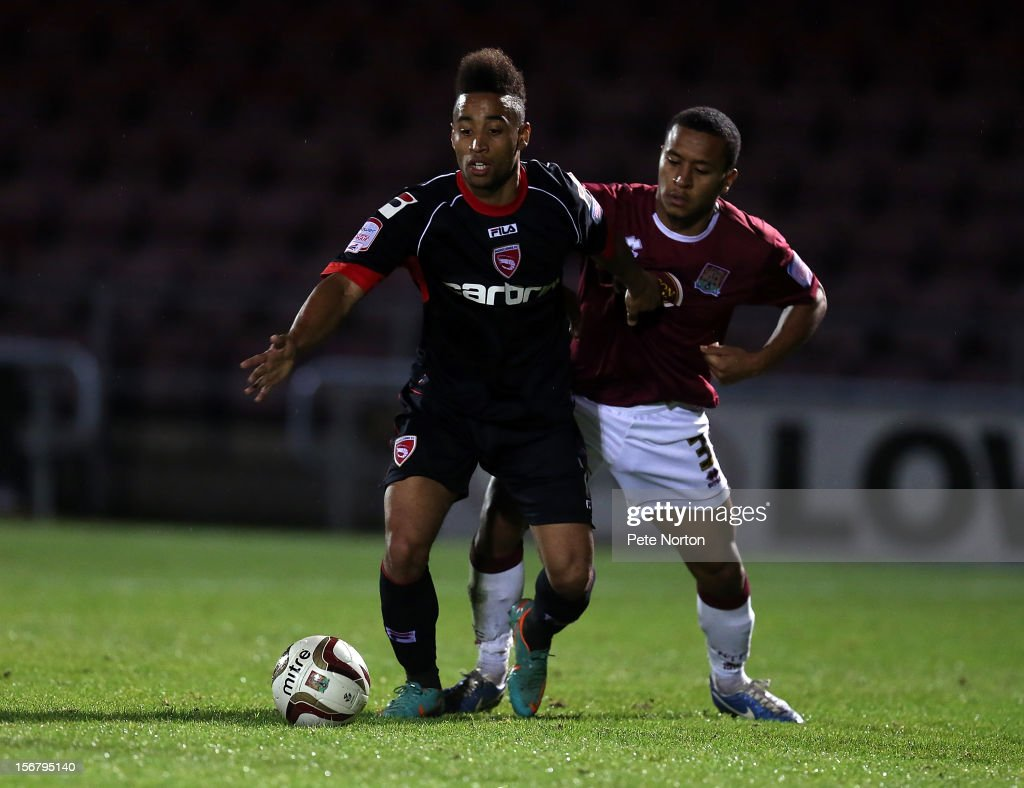 Izak Reid of Morecambe looks to control the ball under pressure from Joe Widdowson of Northampton Town during the npower League Two match between Northampton Town and Morecambe at Sixfields Stadium on November 20, 2012 in Northampton, England.