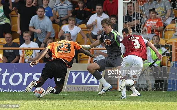 Izale McLeod of Barnet stumbles as he attempts an effort on goal watched by Sam Walker and Ashley Corker of Northampton Town during the npower League...