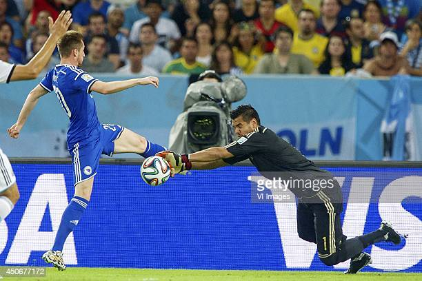 Izet Hajrovic of Bosnia and Herzegovina goalkeeper Sergio Romero of Argentina during the FIFA World Cup 2014 match between Argentina and Bosnia and...