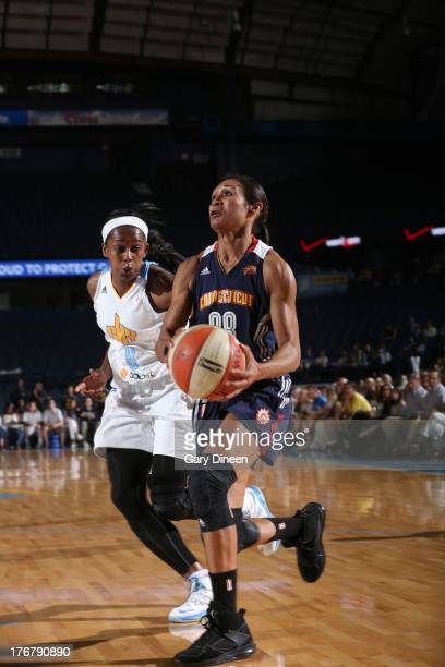 Iziane Castro Marques of the Connecticut Sun drives to the basket past Swin Cash of the Chicago Sky during the game on August 18 2013 at the Allstate...