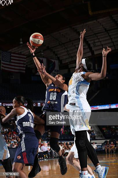 Iziane Castro Marques of the Connecticut Sun goes to the basket past Swin Cash of the Chicago Sky during the game on August 18 2013 at the Allstate...