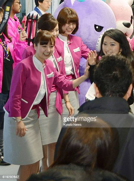 Izumisano Japan Cabin attendants of Peach Aviation Ltd welcome departing passengers on an early morning flight with high fives at Kansai...