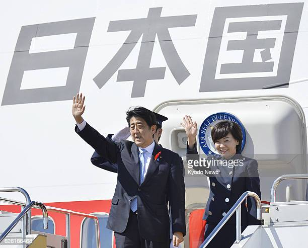 Izumisano Japan Prime Minister Shinzo Abe and his wife Akie wave as they leave from Kansai International Airport in Osaka Prefecture for Bali...