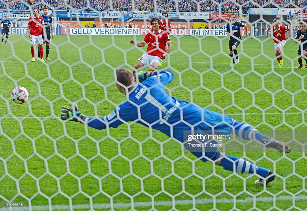 Ja - Cheol Koo (BACK C) of Mainz scores a penalty against goalkeeper Lukas Kruse (FRONT) of Paderborn during the Bundesliga match between SC Paderborn and FSV Mainz 05 at Benteler Arena on August 24, 2014 in Paderborn, Germany.