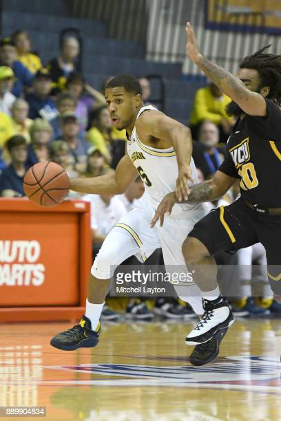 Jaaron Simmons of the Michigan Wolverines dribble sbyJonathan Williams of the Virginia Commonwealth Rams during a consultation college basketball...