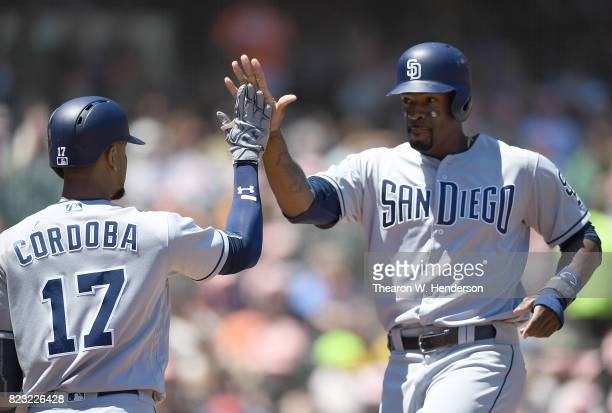 Jabari Blash of the San Diego Padres is congratulated by Allen Cordoba after Blash scored against the San Francisco Giants in the top of the fourth...