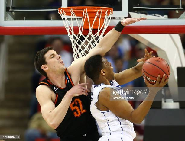Jabari Parker of the Duke Blue Devils goes up for a shot against Daniel Coursey of the Mercer Bears in the first half in the second round of the 2014...
