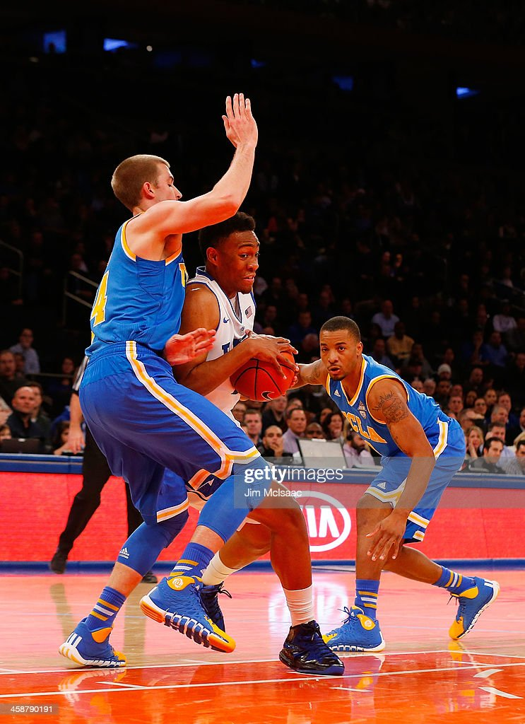 Jabari Parker #1 of the Duke Blue Devils tries to drive to the hoop in the first half against Travis Wear #24 of the UCLA Bruins during the CARQUEST Auto Parts Classic on December 19, 2013 at Madison Square Garden in New York City.