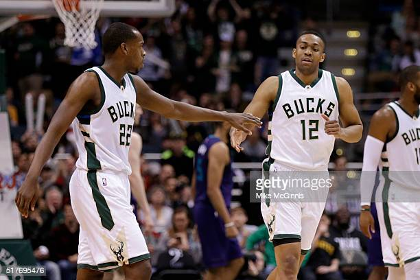 Jabari Parker of the Milwaukee Bucks celebrates with Khris Middleton after slam dunking the basketball during the third quarter against the Charlotte...