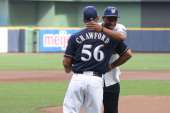 Jabari Parker of the Milwaukee Bucks hugs the Milwaukee Brewers assistant coach Joe Crawford after he threw out the first pitch before the Milwaukee...