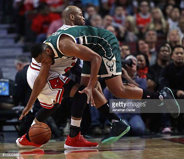 Jabari Parker of the Milwaukee Bucks tries to control a loose ball under pressure from Taj Gibson of the Chicago Bulls during a preseason game at the...