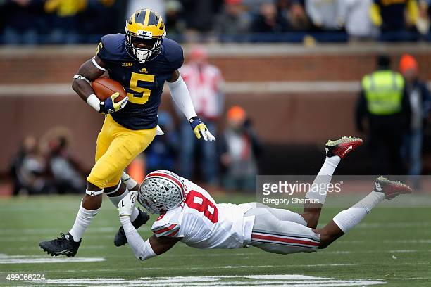 Jabrill Peppers of the Michigan Wolverines eludes the tackle of Gareon Conley of the Ohio State Buckeyes in the first half at Michigan Stadium on...