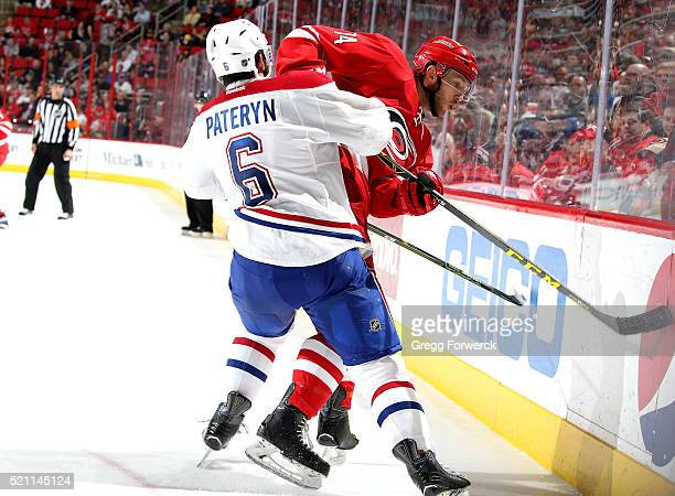 Jaccob Slavin of the Carolina Hurricanes battles along the boards with Greg Pateryn of the Montreal Canadiens during an NHL game at PNC Arena on...