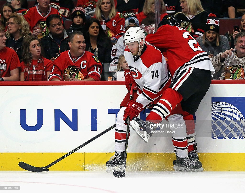 Jaccob Slavin #74 of the Carolina Hurricanes battles for the puck along the boards with Ryan Garbutt #28 of the Chicago Blackhawks at the United Center on December 27, 2015 in Chicago, Illinois.