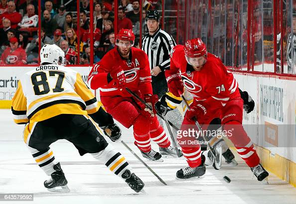 Jaccob Slavin of the Carolina Hurricanes collects the puck ahead of Sidney Crosby of the Pittsburgh Penguins as Jordan Staal looks on during an NHL...
