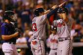 Jace Peterson of the Atlanta Braves celebrates his two run home run with Chase d'Arnaud as catcher Nick Hundley of the Colorado Rockies looks on...