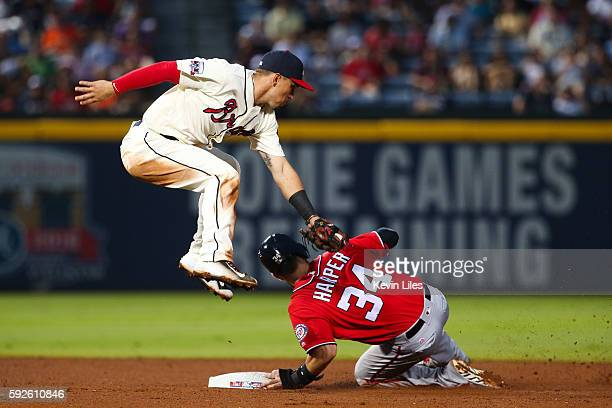 Jace Peterson of the Atlanta Braves misses the tag on Bryce Harper of the Washington Nationals as he steals second during the fourth inning at Turner...