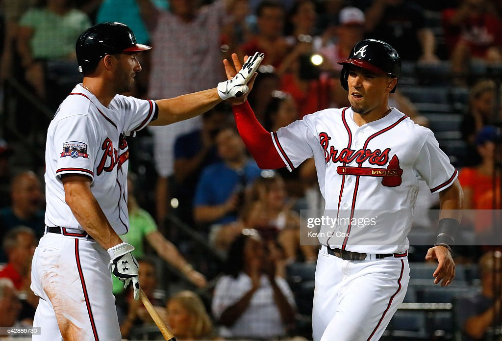Jace Peterson #8 of the Atlanta Braves reacts with Jeff Francoeur #18 after scoring on an RBI single hit by Freddie Freeman #5 in the fifth inning against the New York Mets at Turner Field on June 24, 2016 in Atlanta, Georgia.