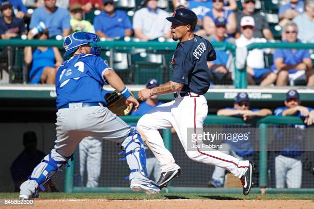 Jace Peterson of the Atlanta Braves scores a run ahead of the throw to Juan Graterol of the Toronto Blue Jays following a single by Anthony Recker in...