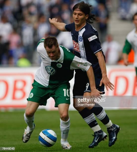 Jacek Krzynowek of Wolfsburg is challenged by Marko Pantelic of Berlin during the Bundesliga match between Hertha BSC Berlin and VfL Wolfsburg at the...