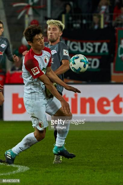 JaCheol Koo of Augsburg and Kevin Kampl of Leipzig battle for the ball during the Bundesliga match between FC Augsburg and RB Leipzig at WWKArena on...