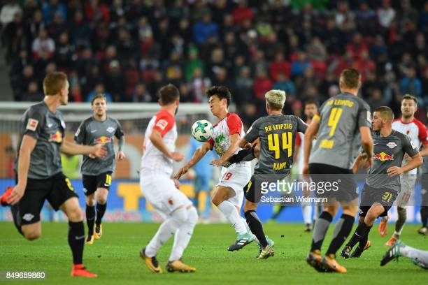 JaCheol Koo of Augsburg and Kevin Kampl of Leipzig compete for the ball during the Bundesliga match between FC Augsburg and RB Leipzig at WWKArena on...