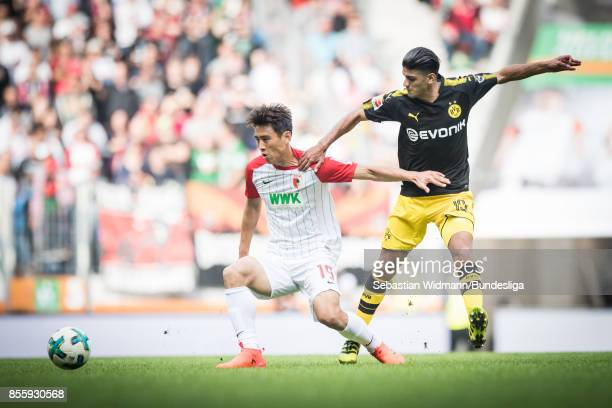JaCheol Koo of Augsburg and Mahmoud Dahoud of Borussia Dortmund compete for the ball during the Bundesliga match between FC Augsburg and Borussia...