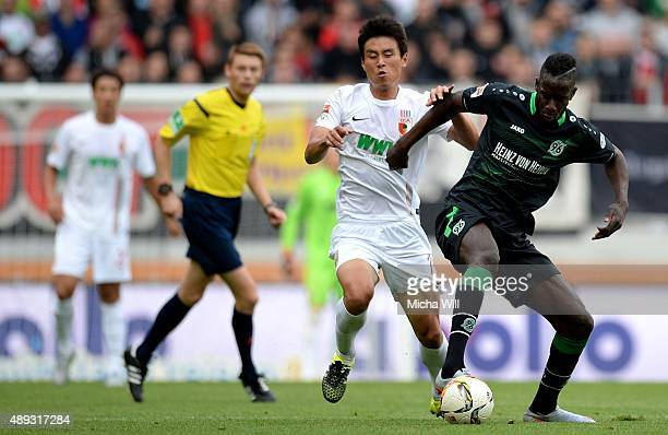 JaCheol Koo of Augsburg and Salif Sane of Hannover tussle for the ball during the Bundesliga match between FC Augsburg and Hannover 96 at WWK Arena...