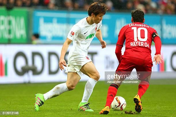 JaCheol Koo of Augsburg battles for the ball with Karim Bellarabi of Leverkusen during the Bundesliga match between FC Augsburg and Bayer Leverkusen...