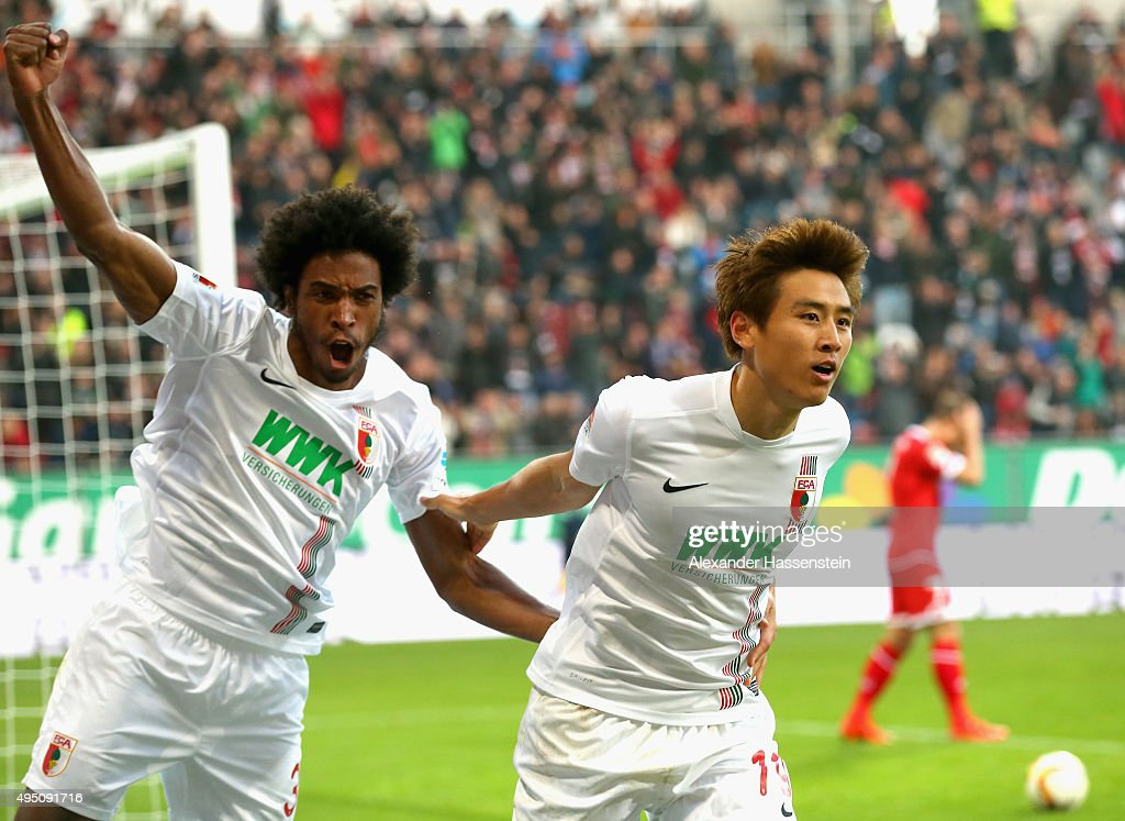Ja-Cheol Koo (L) of Augsburg celebrates scoring the 2nd team goal with his team mate <a gi-track='captionPersonalityLinkClicked' href=/galleries/search?phrase=Caiuby+Francisco+da+Silva&family=editorial&specificpeople=5553672 ng-click='$event.stopPropagation()'>Caiuby Francisco da Silva</a> during the Bundesliga match between FC Augsburg and 1. FSV Mainz 05 at WWK Arena on October 31, 2015 in Augsburg, Germany.