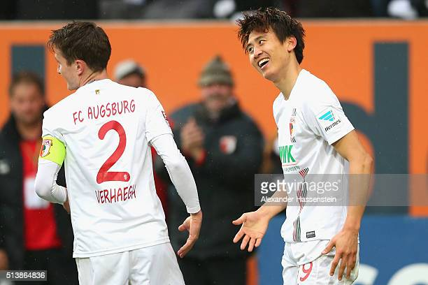 JaCheol Koo of Augsburg celebrates scoring the third goal with his team mate Paul Verhaegh during the Bundesliga match between FC Augsburg and Bayer...