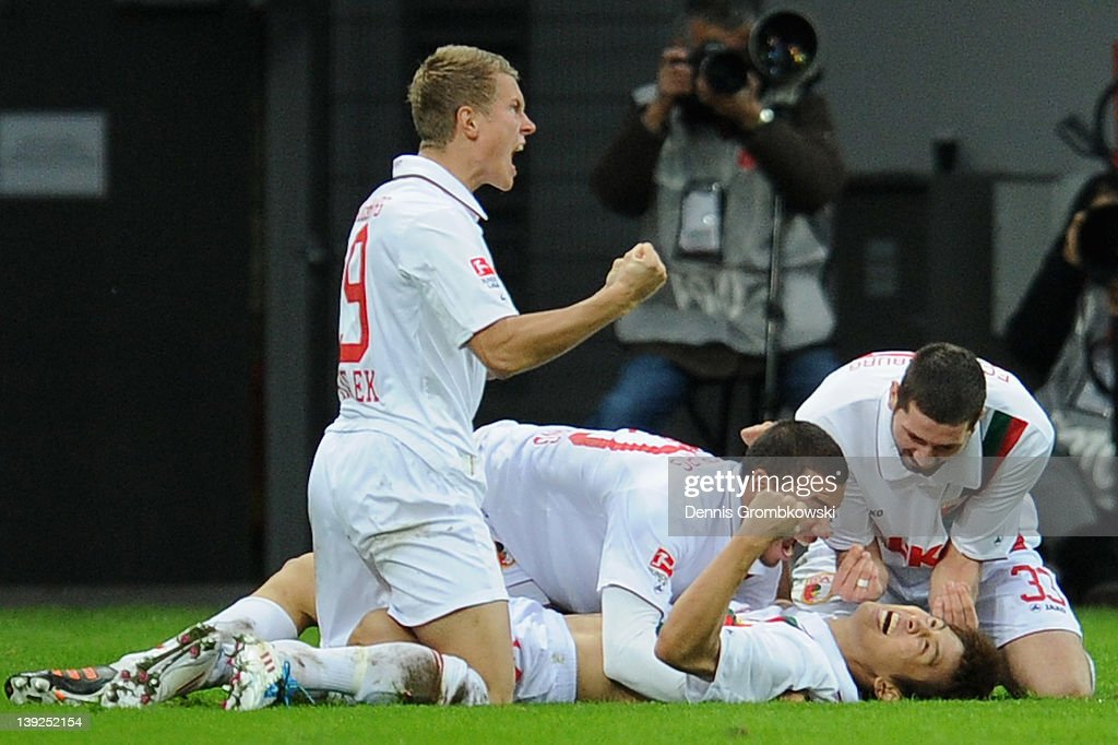 JaCheol Koo of Augsburg celebrates with teammates after scoring his team's first goal during the Bundesliga match between Bayer 04 Leverkusen and FC...