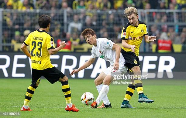 JaCheol Koo of Augsburg challenges Shinji Kagawa of Dortmund and Marcel Schmelzer of Dortmund during the Bundesliga match between Borussia Dortmund...