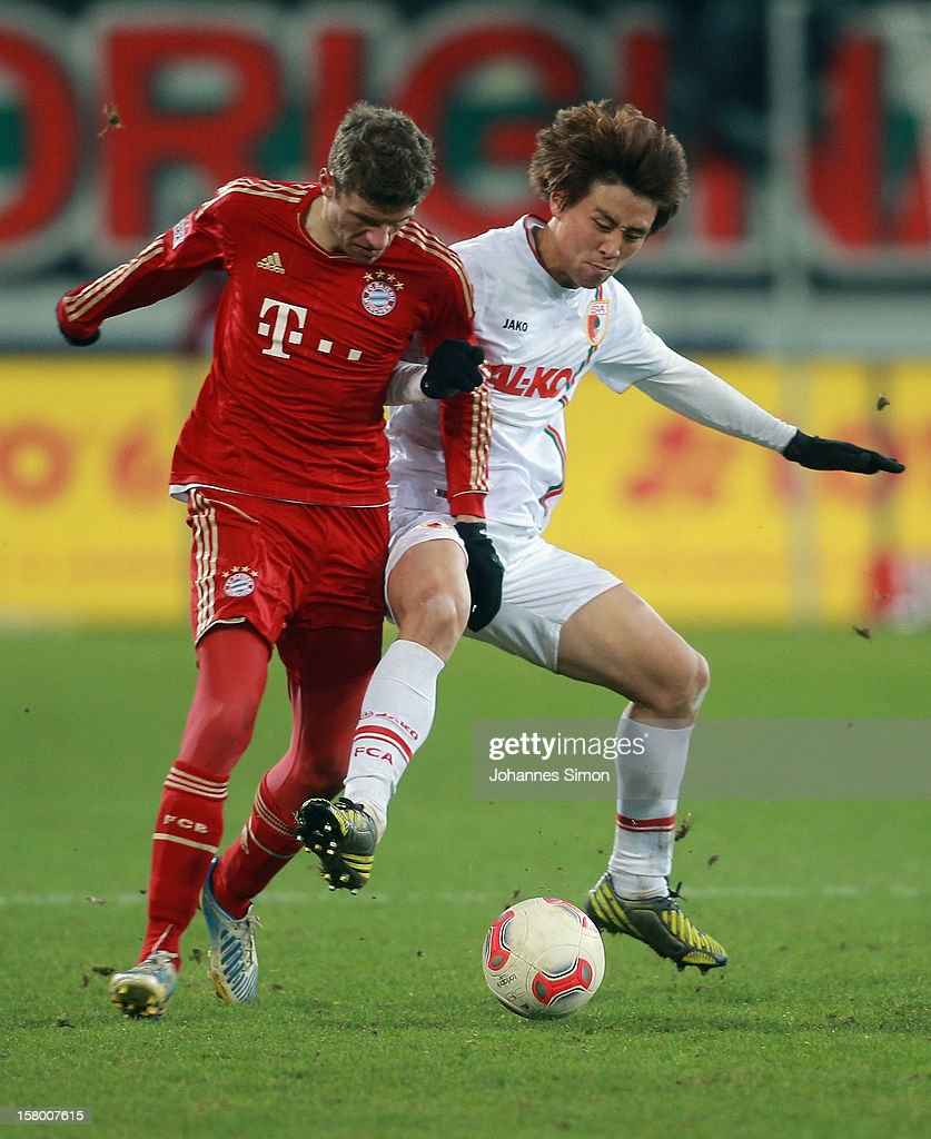 Ja-Cheol Koo (R) of Augsburg fights for the ball with <a gi-track='captionPersonalityLinkClicked' href=/galleries/search?phrase=Thomas+Mueller&family=editorial&specificpeople=5842906 ng-click='$event.stopPropagation()'>Thomas Mueller</a> of Bayern during the Bundesliga match between FC Augsburg and FC Bayern Muenchen at SGL Arena on December 8, 2012 in Augsburg, Germany.