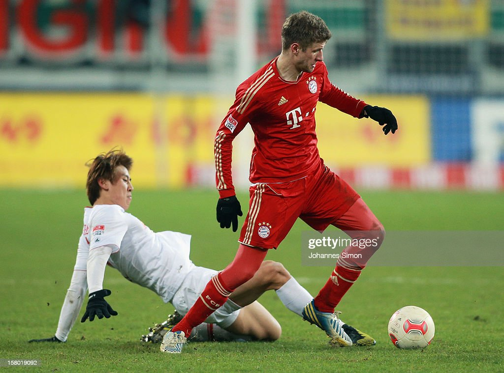 Ja-Cheol Koo (L) of Augsburg fights for the ball with <a gi-track='captionPersonalityLinkClicked' href=/galleries/search?phrase=Thomas+Mueller&family=editorial&specificpeople=5842906 ng-click='$event.stopPropagation()'>Thomas Mueller</a> of Bayern during the Bundesliga match between FC Augsburg and FC Bayern Muenchen at SGL Arena on December 8, 2012 in Augsburg, Germany.