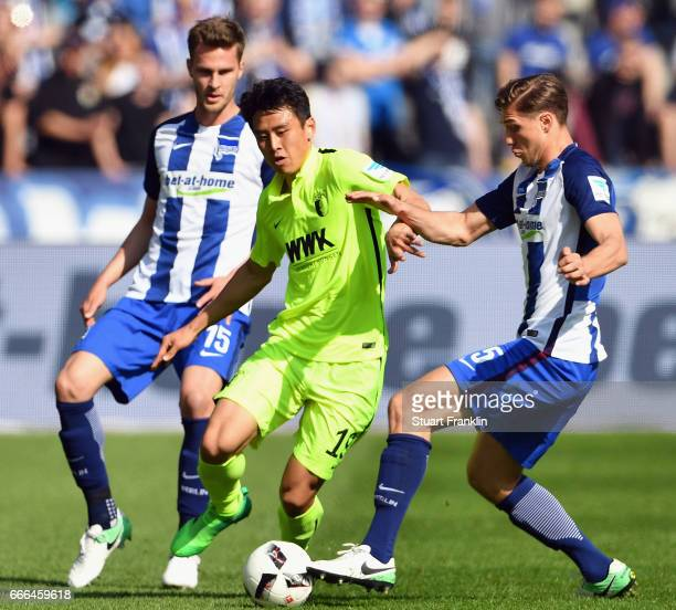 Jacheol Koo of Augsburg is challenged by Sebastian Langkamp and Niklas Stark of Berlin during the Bundesliga match between Hertha BSC and FC Augsburg...