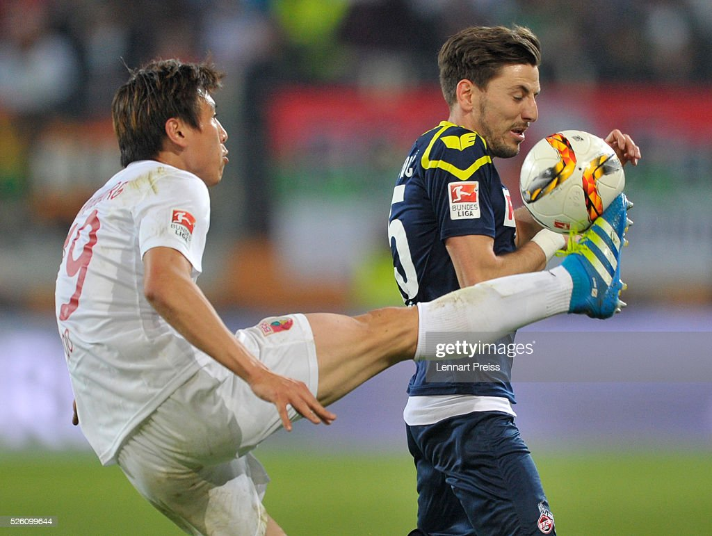Ja-Cheol Koo (L) of FC Augsburg challenges Milos Jojic of 1. FC Koeln during the Bundesliga match between FC Augsburg and 1. FC Koeln at WWK Arena on April 29, 2016 in Augsburg, Germany.