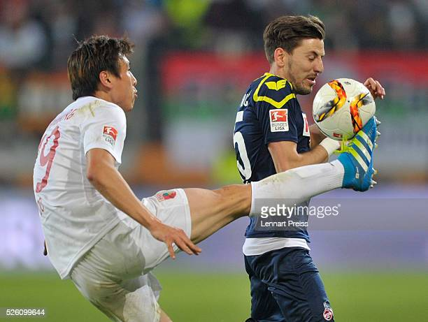 JaCheol Koo of FC Augsburg challenges Milos Jojic of 1 FC Koeln during the Bundesliga match between FC Augsburg and 1 FC Koeln at WWK Arena on April...
