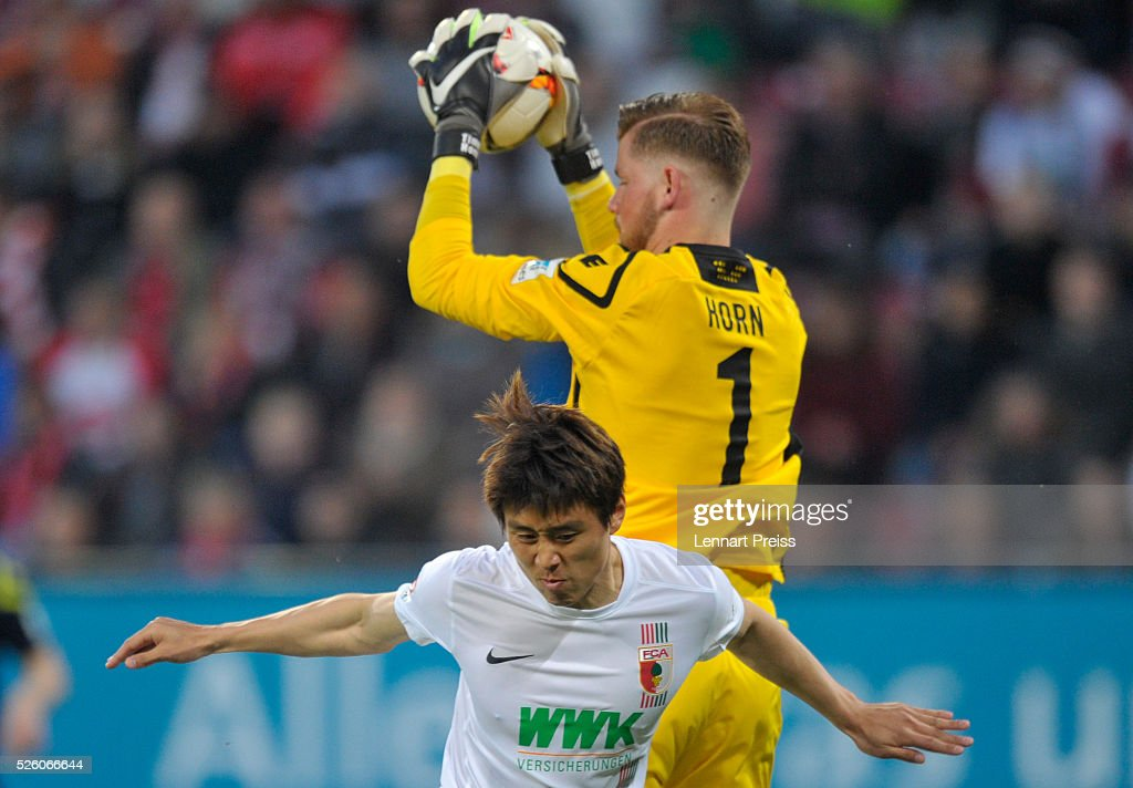 Ja-Cheol Koo (bottom) of FC Augsburg challenges Timo Horn of 1. FC Koeln during the Bundesliga match between FC Augsburg and 1. FC Koeln at WWK Arena on April 29, 2016 in Augsburg, Germany.