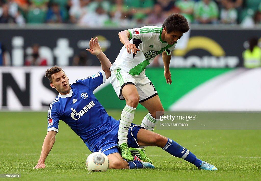 Ja-Cheol Koo (R) of Wolfsburg battles for the ball with <a gi-track='captionPersonalityLinkClicked' href=/galleries/search?phrase=Adam+Szalai&family=editorial&specificpeople=2344504 ng-click='$event.stopPropagation()'>Adam Szalai</a> of Schalke during the Bundesliga match between VfL Wolfsburg and FC Schalke 04 at Volkswagen Arena on August 17, 2013 in Wolfsburg, Germany.