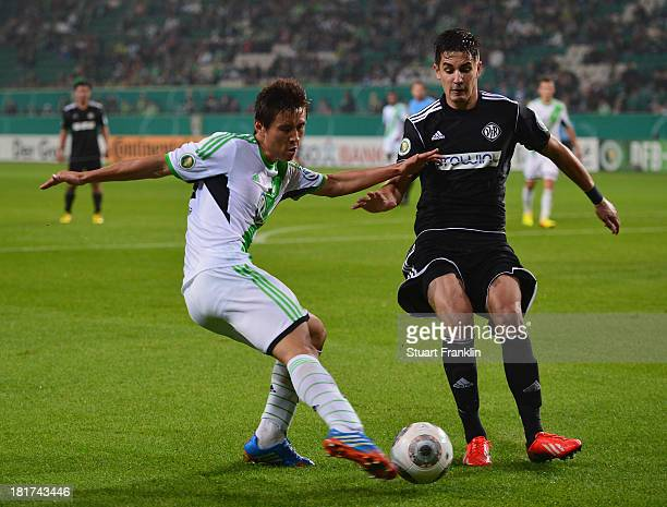 JaCheol Koo of Wolfsburg is challenged by Benjamin Hübner of Aalen during the second round DFB cup match between VfL Wolfsburg and Vfr Aalen at...