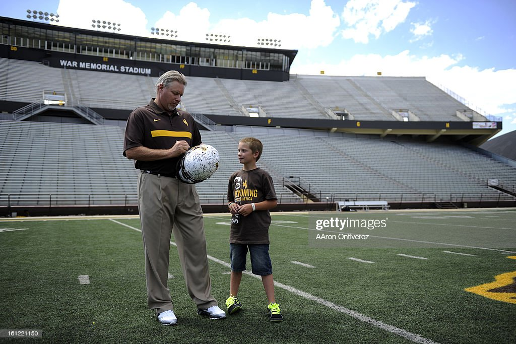 Jachob Fuss of Green River gets an autograph from Wyoming head coach Dave Christensen during UW's media day at Jonah Field at War Memorial Stadium in...