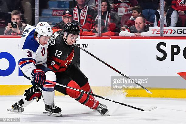 Jack Ahcan of Team United States and Julien Gauthier of Team Canada battle for the puck during the 2017 IIHF World Junior Championship gold medal...