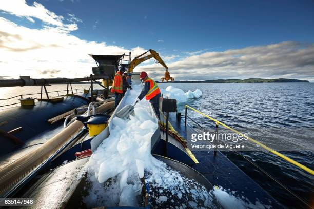 Jack and Austin Randell are cutting into smaller peices of ice the 500 kg grabbed from the iceberg The pieces of ice are going through the pipe into...