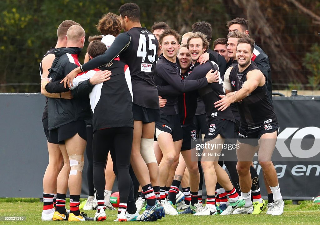 Jack Billings (C) of the Saints and his teammates embrace during atraining exercise during a St Kilda Saints AFL training session at Linen House Oval on August 17, 2017 in Melbourne, Australia.