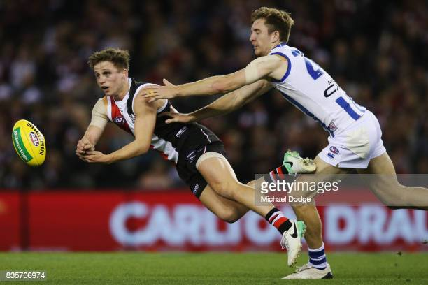 Jack Billings of the Saints handballs from Daniel Nielson of the Kangaroos during the round 22 AFL match between the St Kilda Saints and the North...