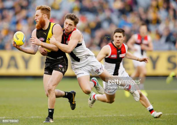 Jack Billings of the Saints tackles Nick Vlastuin of the Tigers during the round 23 AFL match between the Richmond Tigers and the St Kilda Saints at...