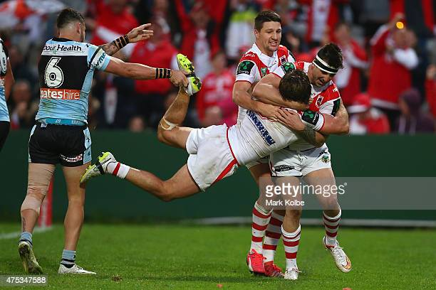 Jack Bird of the Sharks holds the leg of Mitch Rein of the Dragons as he celebrates with his team mates after scoring a try during the round 12 NRL...